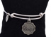 "Courage Bangle Bracelet Adjustable silver-plated bracelet features a round charm with the scripted word ""Courage""."